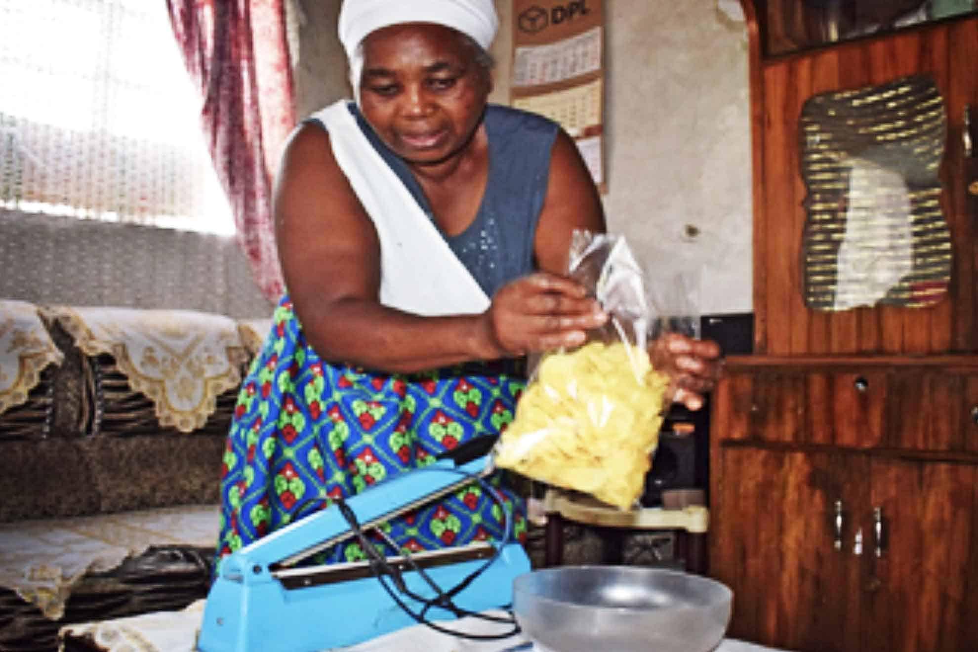 Wamuyu, business owner packaging her crisps.