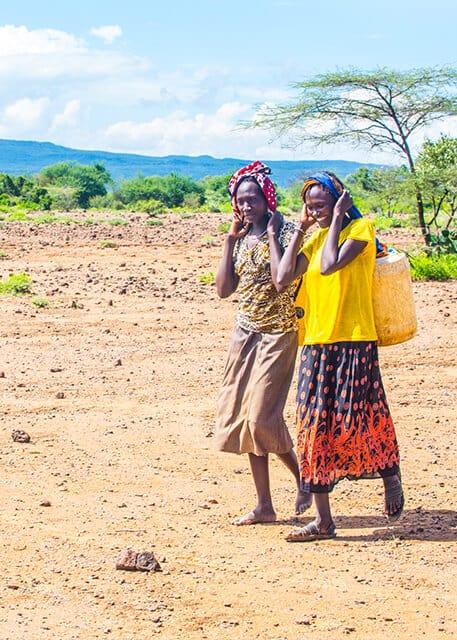 Two Kenyan woman carrying water jerry water
