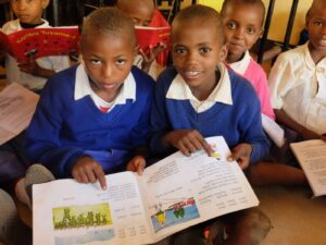 Pupils sitting in the class while reading and looking for the pictures from the book.